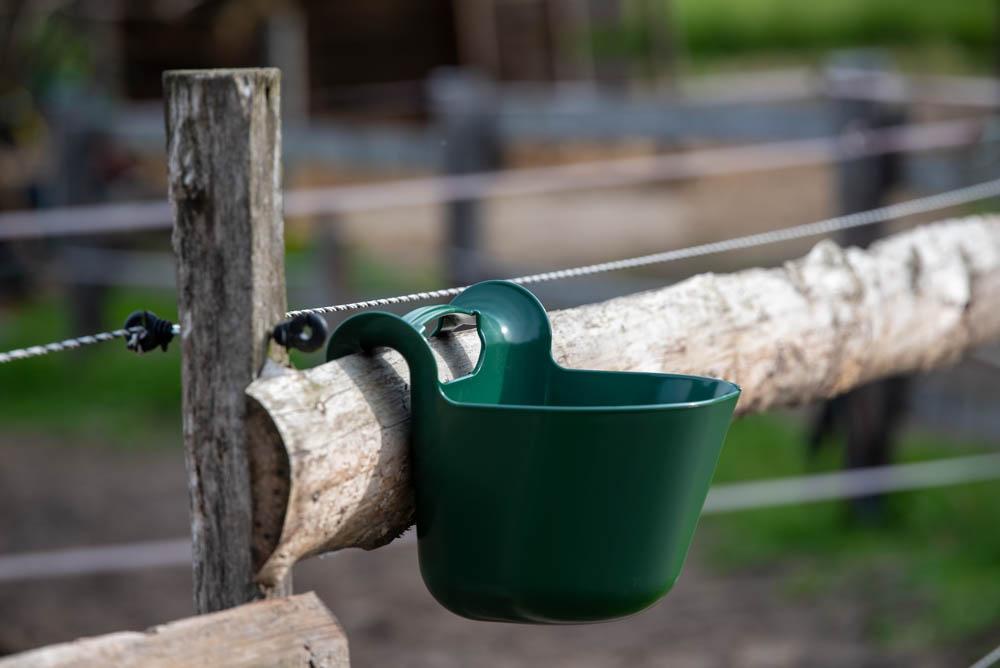 tragbarer Turnierfuttertrog von Horizont an einem Weidezaun aus Holz