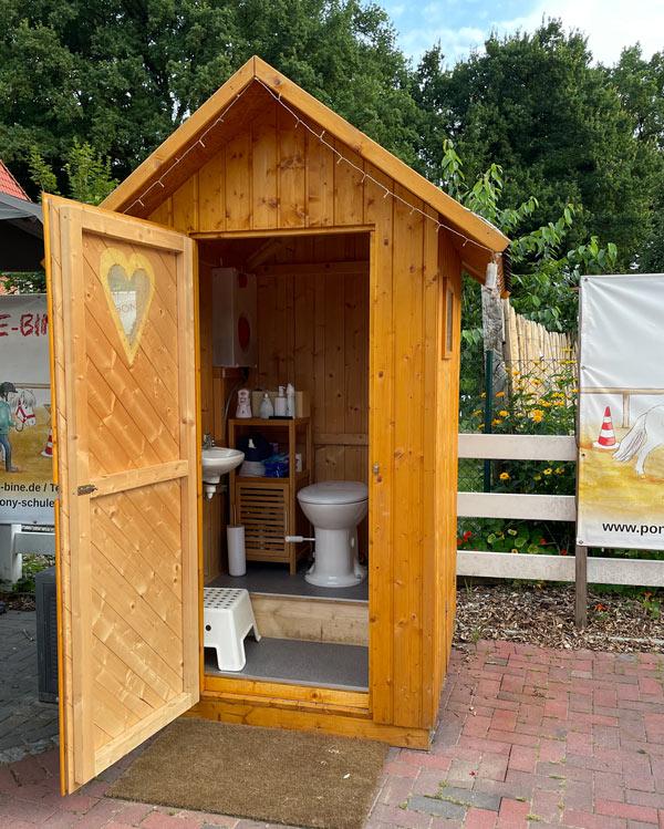 WC-Häuschen mit CampingWC an einem Stall